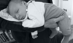 Monthly baby sleeping on the arm of his father's hand, position to help colic